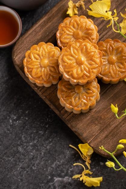 Mooncake, moon cake voor mid-autumn festival, concept van traditionele feestelijke gerechten op zwarte leisteen tafel met thee en gele bloem, close-up. Premium Foto