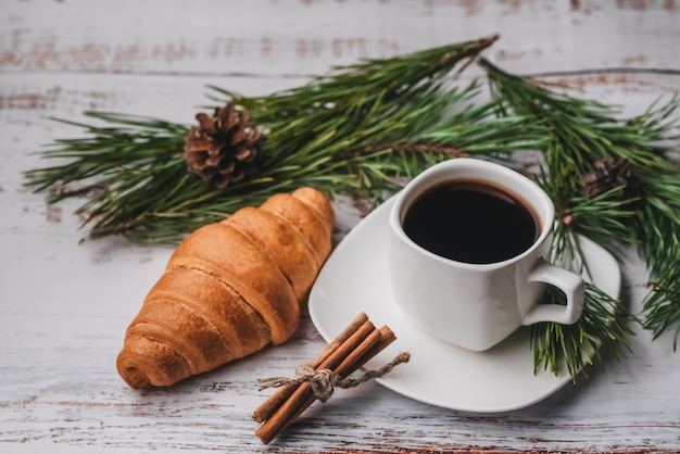 Morning christmas-ontbijt met een kopje koffie en een croissant op een houten tafel Premium Foto