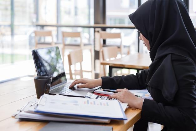 Moslim bedrijfsmensen die zwarte hijab dragen, die in koffiewinkel werken. Premium Foto