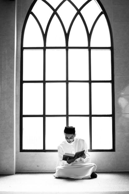 Moslim man die de koran bestudeert Gratis Foto