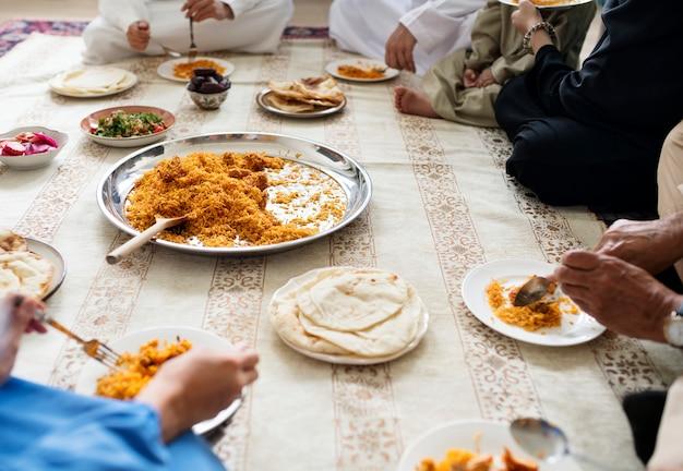 Moslimfamilie die diner op de vloer hebben Premium Foto