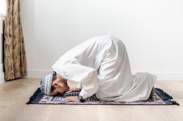 Moslimjongen die in sujud-houding bidden Premium Foto
