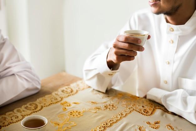 Moslimmannen die een kop thee hebben Gratis Foto