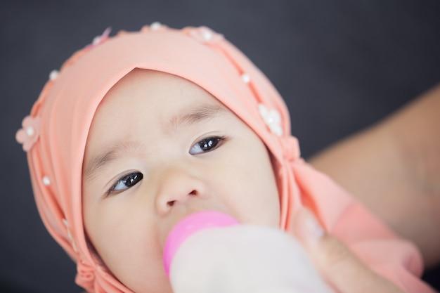 Moslimmoeder die haar baby voedt met een fles melk. Premium Foto
