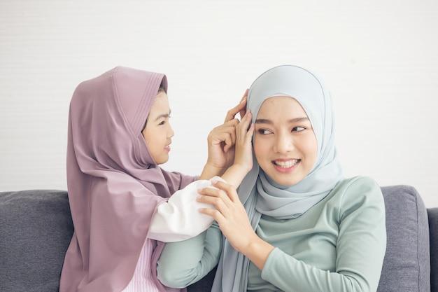 Moslimmoeder in hijab is haar dochtertje dat in de woonkamer zit. liefdevolle relatie Premium Foto