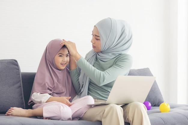 Moslimmoeder in hijab is haar dochtertje met computer in de woonkamer. liefdevolle relatie Premium Foto
