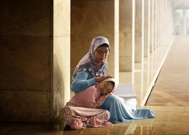Moslimmoeder leert haar dochter koran lezen Premium Foto