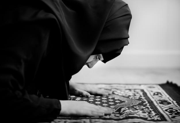 Moslimvrouw die in sujud-houding bidden Gratis Foto