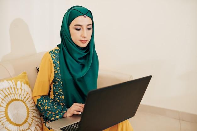 Moslimvrouw die op lapotp werkt Premium Foto