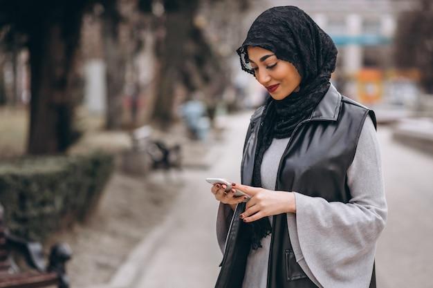 Moslimvrouw die telefoon buiten in de straat met behulp van Gratis Foto