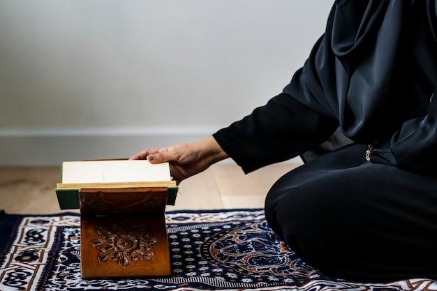 Moslimvrouw die van de koran lezen Premium Foto