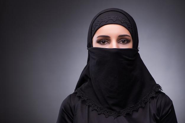 Moslimvrouw in zwarte kleding tegen donkere achtergrond Premium Foto