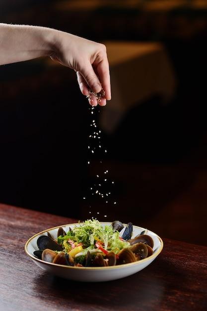 Mosselen met sesamzaden in een plaat op een houten achtergrond Premium Foto