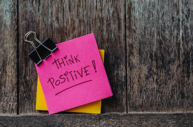 Motivatie denk positieve slogan notitieblokken en paperclip op oude houten achtergrond Premium Foto
