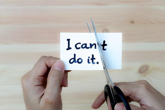 Motivatieconcept, vrouwenhanden die kaart houden die ik het met schaar kan doen. Premium Foto