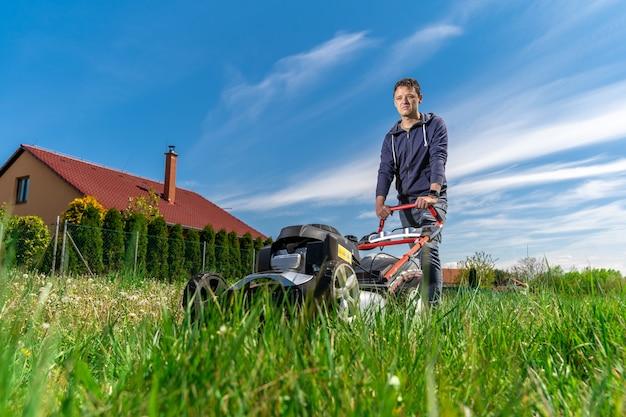 Motormaaier om het gazon naast de gezinswoning te maaien Premium Foto