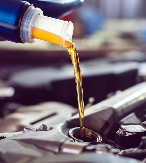 Motorolie gieten naar automotor. Premium Foto