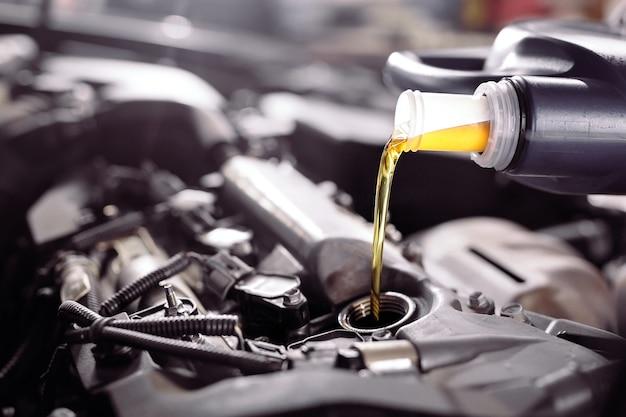 Motorolie gieten naar motor van een auto. Premium Foto