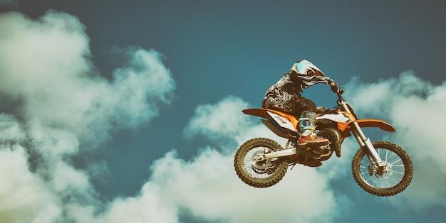 Motorrijder die op blauwe hemel vliegt. extreem concept, verspringen op een motorfiets. Premium Foto