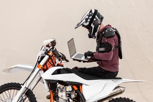 Motorrijder het doorbladeren laptop in de woestijn Gratis Foto