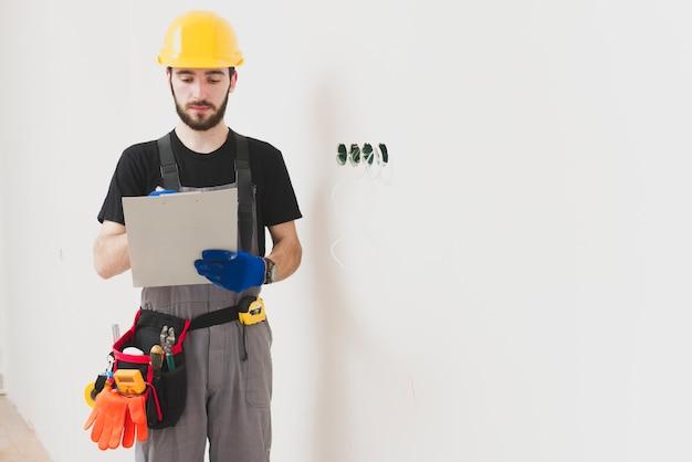 Mounter met tablet aan de muur Gratis Foto