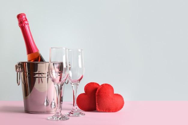 Mousserende wijn, rode harten en wijnglazen voor valentijnsdagfeest voor twee. wenskaart. Premium Foto