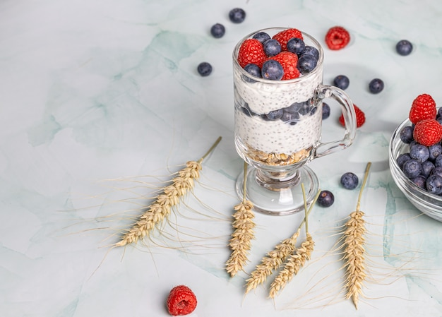 Muesli met bessen en chiazaden op een licht marmeren tafel Premium Foto