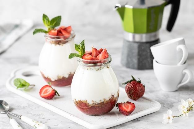 Muesli met yoghurt en aardbeien in een glazen pot. Premium Foto