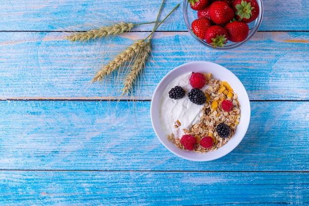 Muesli met yoghurt en fruit op houten tafel Premium Foto