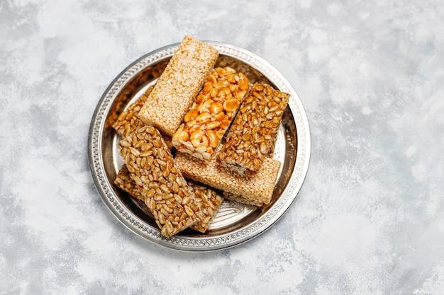 Mueslireep. gezonde zoete dessertsnack. sesam, pinda, zonnebloem in honing. gozinaki is georgisch nationaal eten, oosters zoet. bovenaanzicht op beton Gratis Foto
