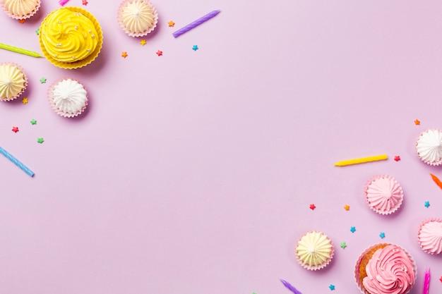Muffins; kaarsen; aalaw en hagelslag op de hoek van roze achtergrond Gratis Foto