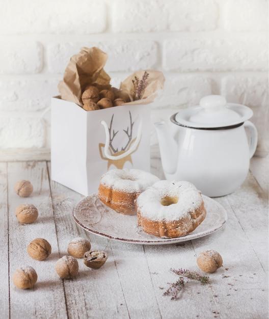Muffins, noten en theepot op witte tafel Premium Foto