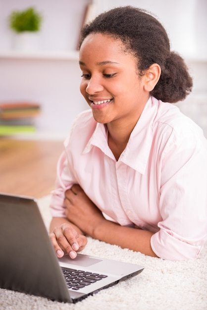 Mulatschoolmeisje die op het tapijt leggen en laptop met behulp van. Premium Foto