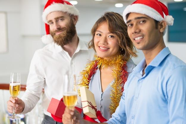 Multi-etnisch commercieel team dat kerstmis champagne drinkt Gratis Foto