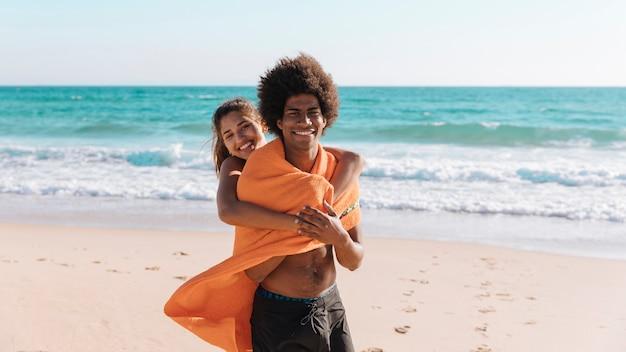 Multi-etnisch paar dat op strand omhelst Gratis Foto