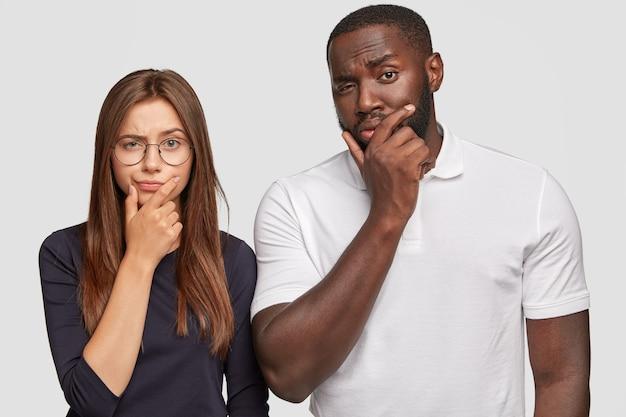 Multi-etnisch vriendschapsconcept. nadenkende twijfelachtige blanke vrouw en knappe zwarte man houden kin vast, hebben uitdrukkingen in verwarring gebracht Gratis Foto