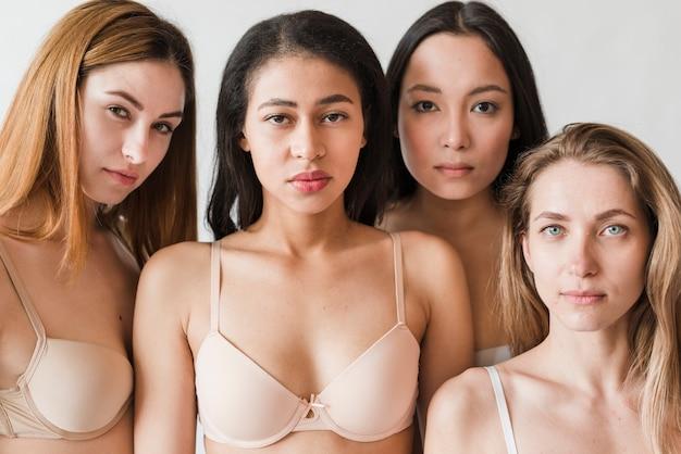 Multi-etnische ernstige jonge vrouwen die bustehouders dragen die camera bekijken Gratis Foto