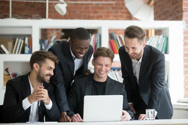 Multi-etnische glimlachende zakenlieden in kostuums die op laptop iets grappig letten Gratis Foto