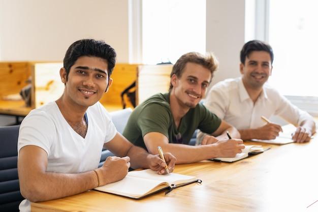 Multi-etnische groep gelukkige studenten die in klaslokaal stellen Gratis Foto