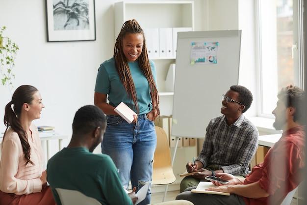 Multi-etnische groep mensen zitten in de cirkel tijdens de bespreking van zakelijk project in kantoor, focus op lachende afro-amerikaanse vrouw in gesprek met collega's Premium Foto