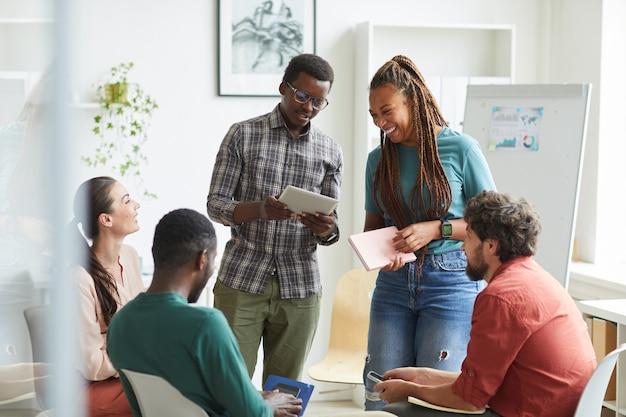 Multi-etnische groep mensen zitten in de cirkel tijdens de bespreking van zakelijk project in kantoor, focus op lachende afro-amerikaanse vrouw praten met collega opstaan Premium Foto
