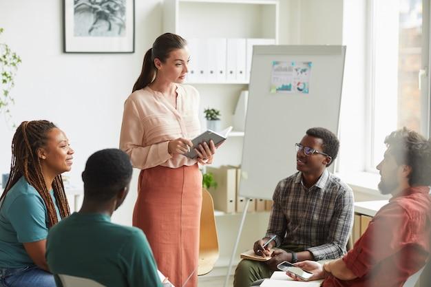 Multi-etnische groep mensen zitten in de cirkel tijdens het bespreken van de strategie voor zakelijk project in kantoor, focus op vrouwelijke manager die instructies geeft Premium Foto
