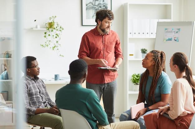 Multi-etnische groep mensen zitten in een cirkel tijdens het bespreken van zakelijk project in kantoor, focus op lachende beaqrded manager praten met collega's Premium Foto