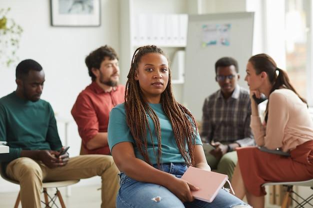 Multi-etnische groep mensen zitten in een cirkel tijdens het bespreken van zakelijk project in kantoor Premium Foto