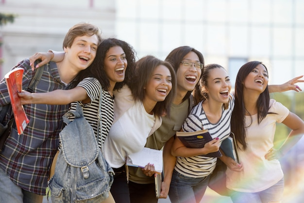 Multi-etnische groep van jonge gelukkige studenten permanent buitenshuis Gratis Foto