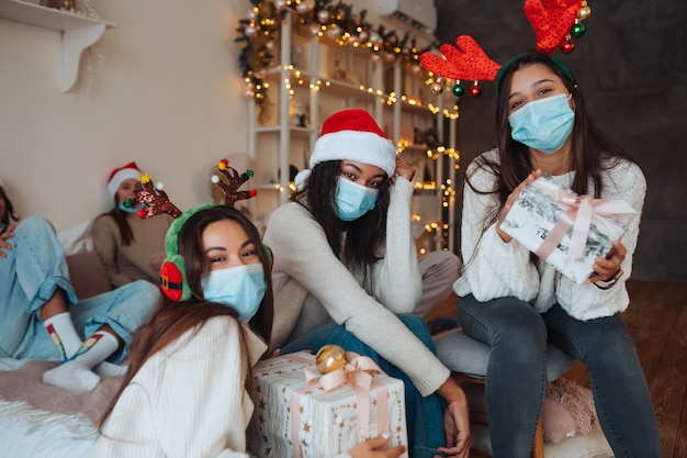 Multi-etnische groep vrienden in santa hoeden glimlachen en poseren voor de camera met geschenken in handen. het concept van het vieren van nieuwjaar en kerstmis onder coronavirusbeperkingen. vakantie in quarantaine Gratis Foto