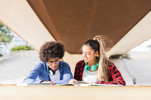Multi-etnische jonge studenten die samen op campus bestuderen Gratis Foto
