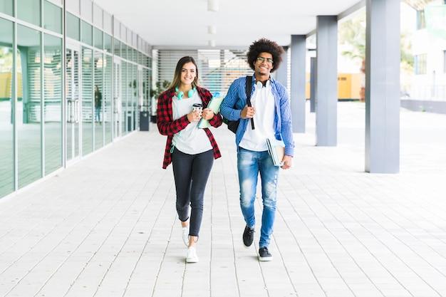 Multi etnische mannelijke en vrouwelijke studenten die samen in universitaire campus lopen Gratis Foto