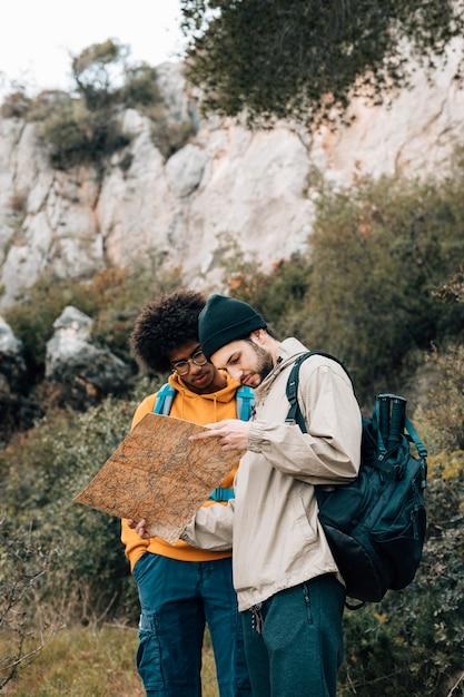 Multi-etnische mannelijke wandelaar die de bestemming op kaart in het bos vinden Gratis Foto