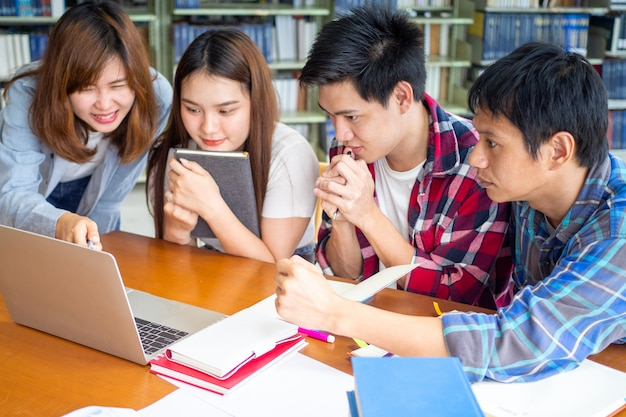 Multi-etnische studenten die testresultaten controleren, die laptop het scherm bij bibliotheek bekijken. Premium Foto